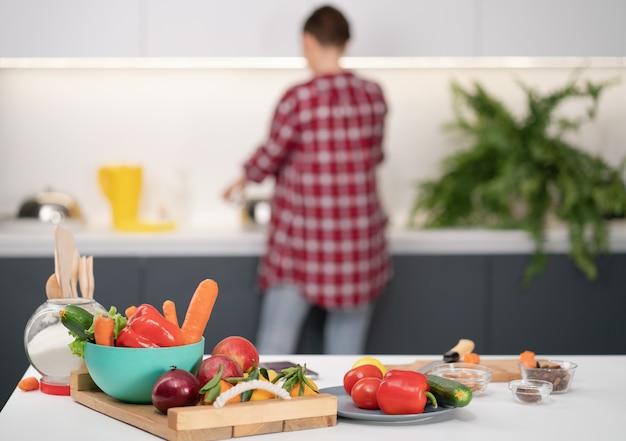 Mãe cozinhando o jantar para uma família amorosa lavando ingredientes em pé, de costas para a câmera