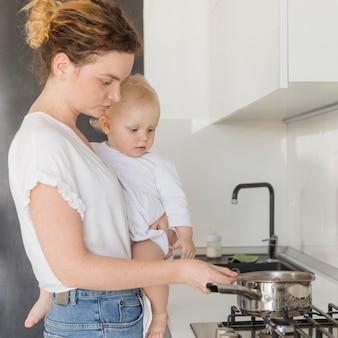 Mãe cozinhando, segurando o bebê