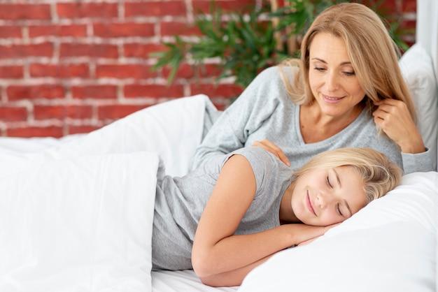 Mãe cuidadosa, assistindo a filha escorregar