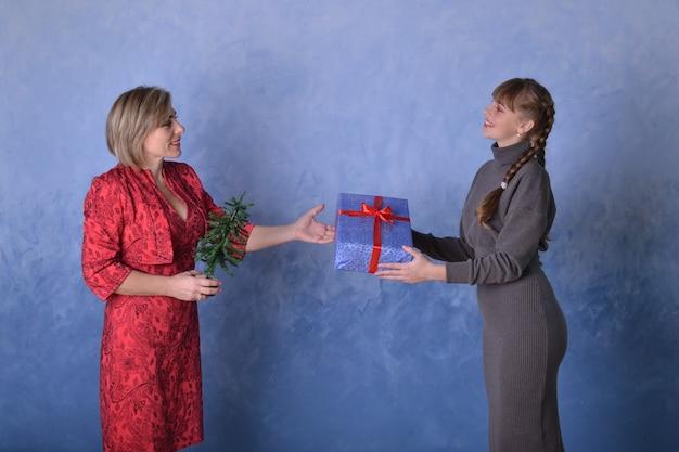 Mãe dá à filha um presente azul com uma fita vermelha em um fundo azul