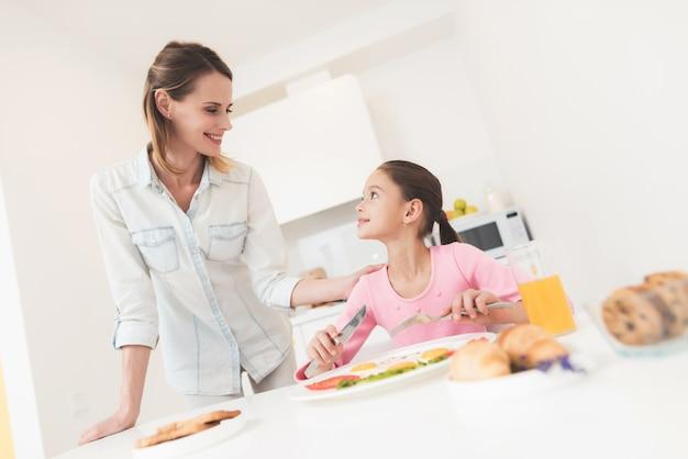 Mãe dá o café da manhã da filha dela. eles estão na cozinha brilhante