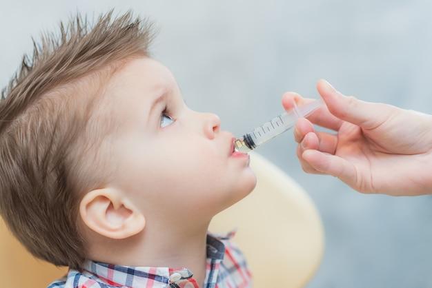 Mãe dá o óleo de peixe bebê através de uma seringa