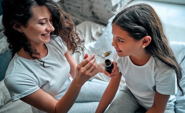 Mãe dando a filha xarope para tosse na cama em casa.