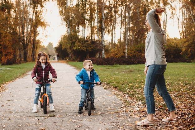 Mãe dando a largada enquanto o filho e a filha riem esperando para seguir em frente