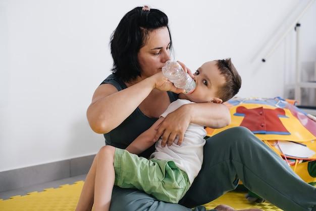 Mãe dando água para criança deficiente