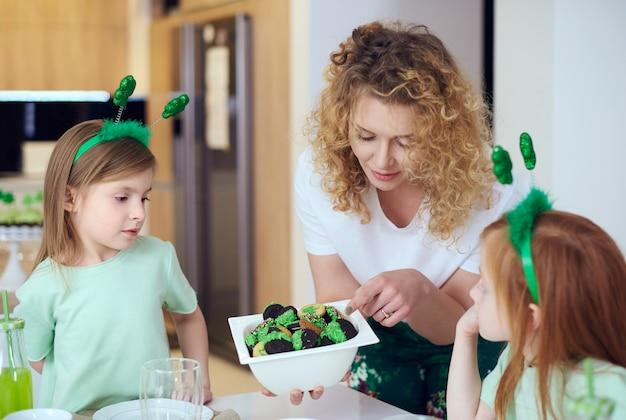 Mãe dando biscoitos aos filhos