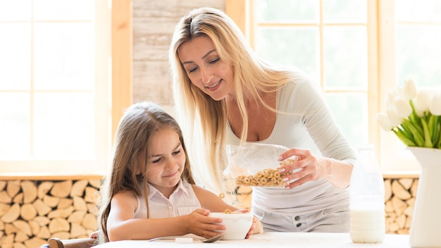 Mãe dando cereais no café da manhã para filha