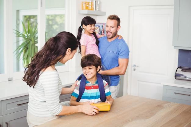 Mãe dando lancheira para filho e pai com filha