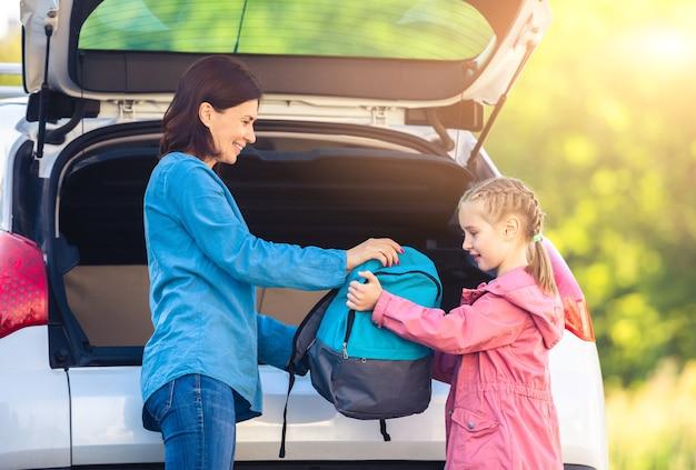 Mãe dando mochila para filha do carro
