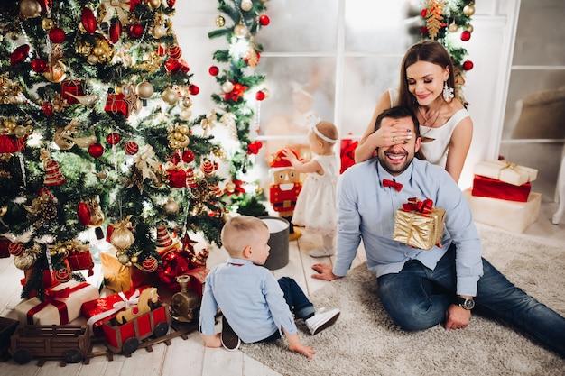 Mãe dando presente para o marido na árvore de natal