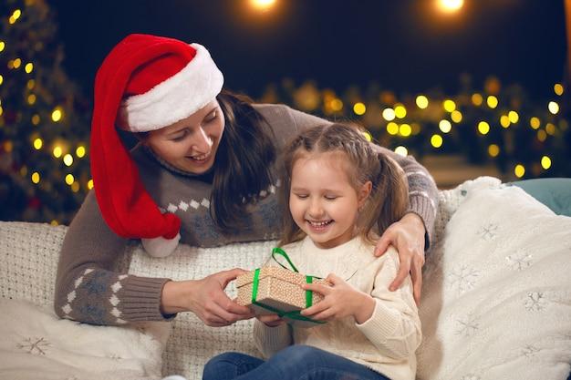 Mãe dando um presente para sua filhinha no sofá
