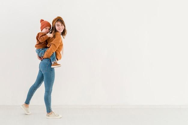 Mãe de alto ângulo, oferecendo cavalinho para seu filho