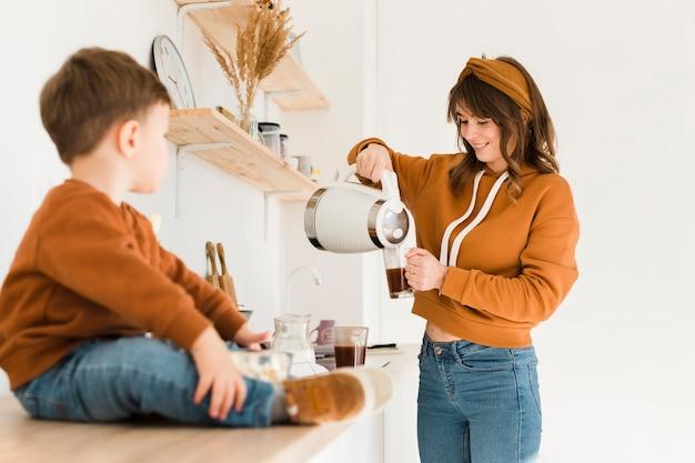 Mãe de alto ângulo preparando café