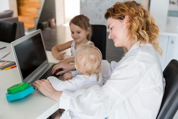 Mãe de alto ângulo, trabalhando com bebê