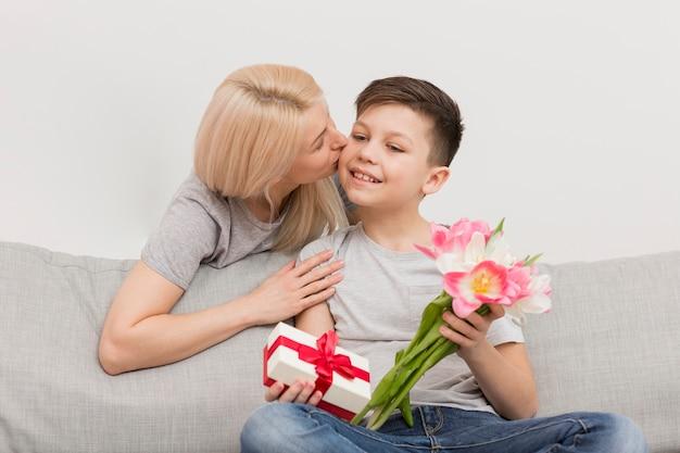 Mãe de baixo ângulo, beijando o filho para presentes