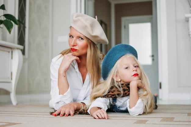 Mãe de cabelos longos justo feliz engraçado jovem e sua linda garota vestida moda família olhar se divertindo juntos deitado no chão na sala de estar, estilo de vida feliz
