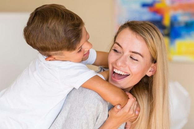 Mãe de close-up, brincando com seu filho na sala de estar