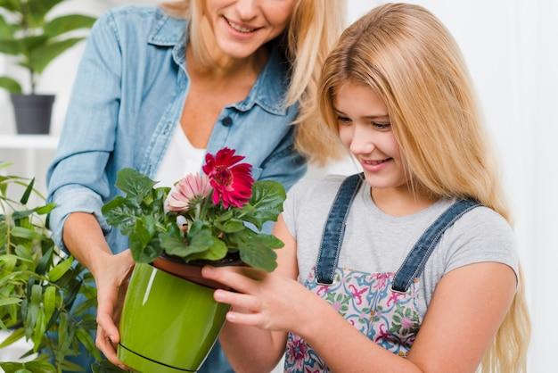Mãe de close-up e filha cuidar de flores