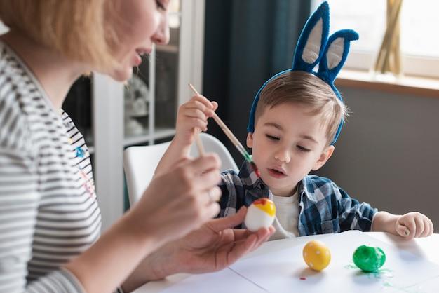 Mãe de close-up, mostrando o menino como pintar ovos
