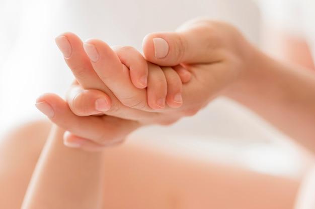 Mãe de close-up, segurando a mão do bebê