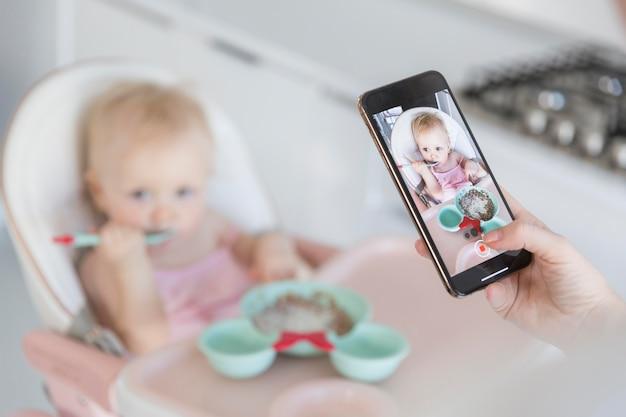 Mãe de close-up, tirando foto de bebê