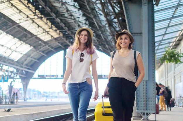 Mãe de duas mulheres e filha adolescente andando com bagagem na estação ferroviária. pessoas aguardando a chegada de trens