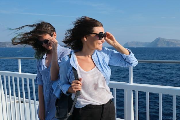Mãe de duas mulheres e filha adolescente curtindo uma viagem marítima em um navio de cruzeiro, cabelos voando ao vento