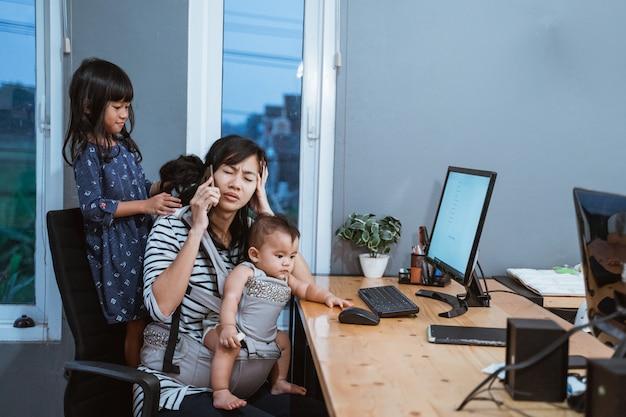 Mãe de estresse enquanto trabalha em casa
