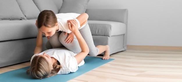 Mãe de exercício força com menina