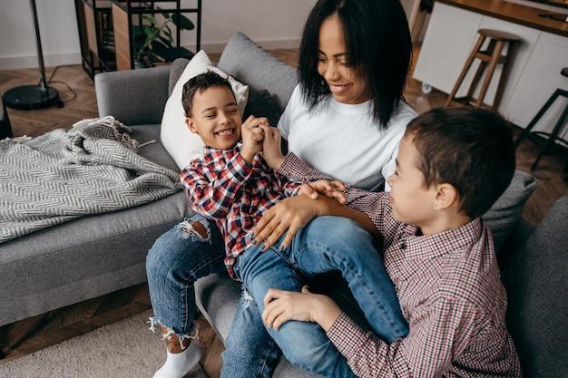 Mãe de família afro-americana feliz e dois filhos brincando e se divertindo em casa juntos
