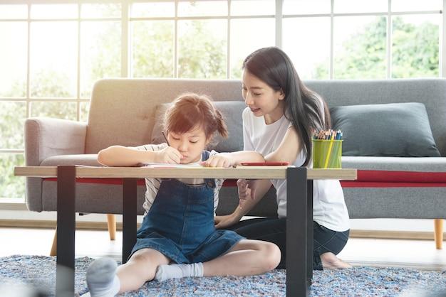 Mãe de família asiática e menina aprendendo e escrevendo no livro com lápis fazendo lição de casa.