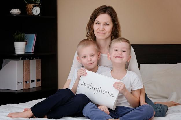 Mãe de família com filhos sentados em uma cama em casa, segurando um papel branco com o texto estadia em casa. quarentena de coronavírus