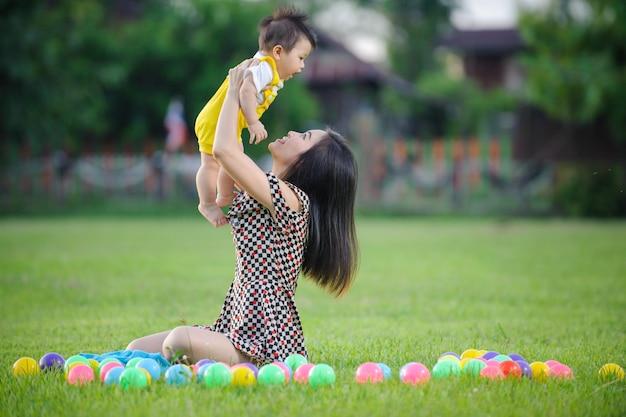Mãe de família feliz e bebê brincando na grama