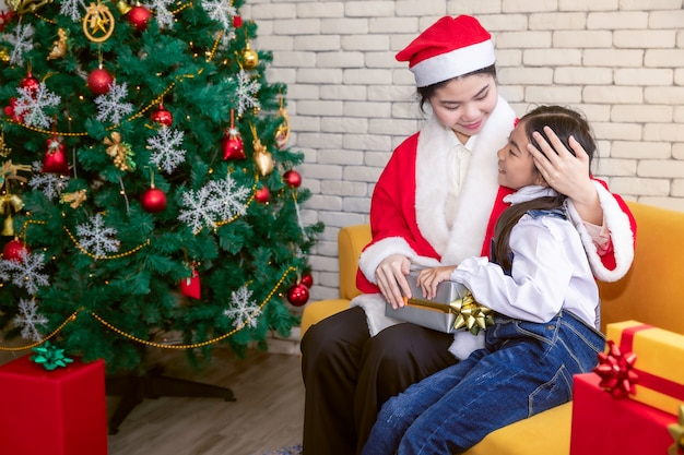 Mãe de família feliz e bebê filha abraçam e segurando com caixa de presente na época do natal.