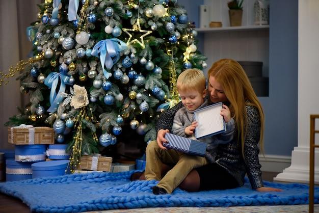 Mãe de família feliz e bebê pequeno filho brincando em casa nas férias de natal. feriados de ano novo