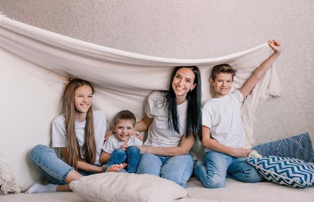 Mãe de família feliz e crianças pequenas riem alegremente sentados no sofá coberto com um cobertor branco. felicidade familiar fim de semana divertido