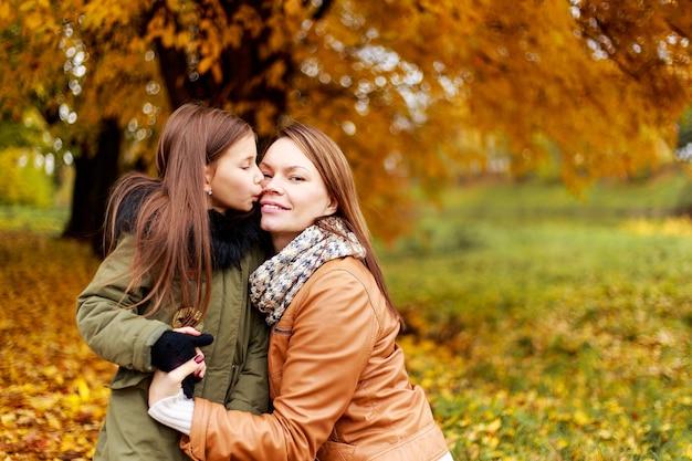 Mãe de família feliz e filha pequena brincando na caminhada de outono.
