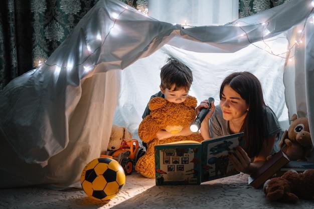 Mãe de família feliz e filho lendo um livro com uma lanterna em uma tenda em casa. conceito de familia