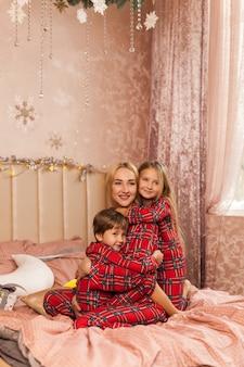Mãe de família feliz e filhos na manhã de natal na cama de pijama
