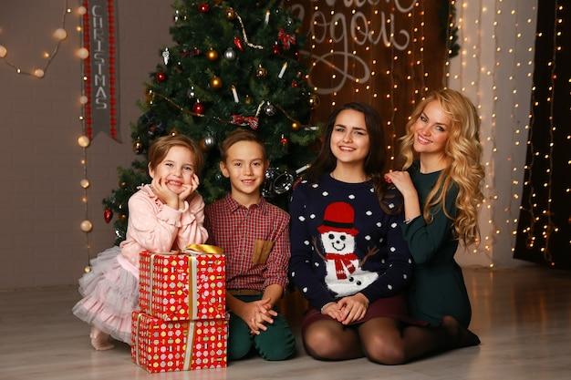 Mãe de família feliz e filhos no natal para a árvore de natal com presentes.