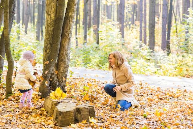 Mãe de família feliz e menina brincando e jogando folhas no outono parque ao ar livre