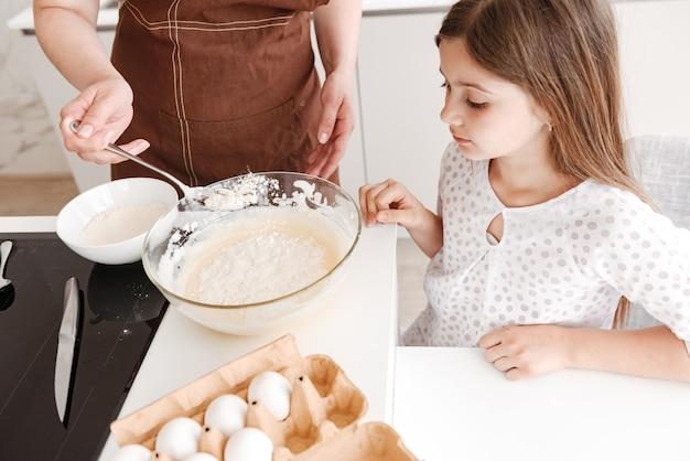 Mãe de família feliz e menina cozinhando na cozinha usando farinha com ovos e amassando a massa com colher