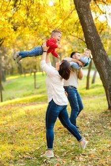 Mãe de família feliz, pai e bebê gêmeos estão brincando e rindo no parque