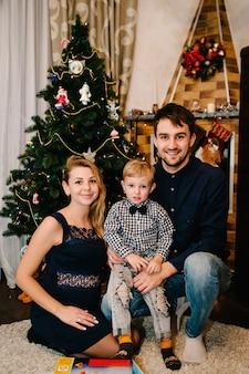 Mãe de família feliz, pai e filho perto da árvore de natal com presentes e lareira.