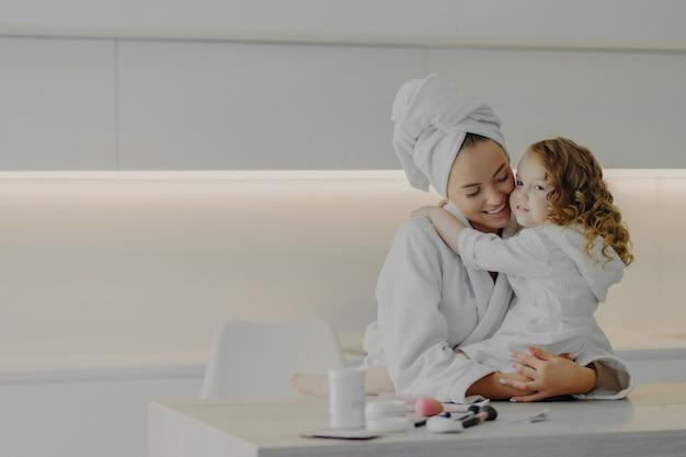 Mãe de família jovem e filha pequena em roupões de banho brancos, abraçando-se após procedimentos de spa em pé na cozinha moderna branca em casa. linda mãe amorosa passando um tempo com a criança pela manhã