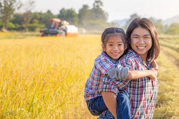 Mãe de fazendeiro dando carona à filha em um campo de arroz amarelo-dourado com trator colheitadeira