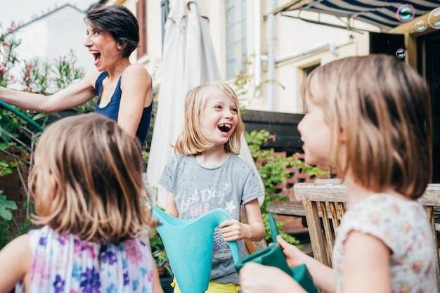 Mãe de jardinagem em casa com três filha