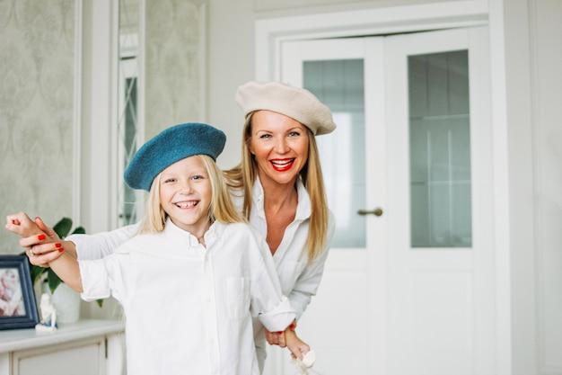 Mãe de jovem feliz justo cabelos longos engraçado e sua filha se divertindo juntos na sala de estar, estilo de vida familiar feliz