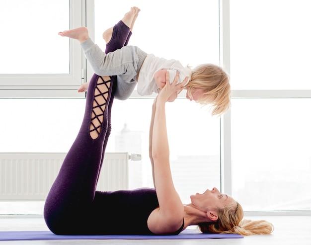 Mãe de jovem loira praticando ioga com a criança e segurando o filho nos braços estendidos