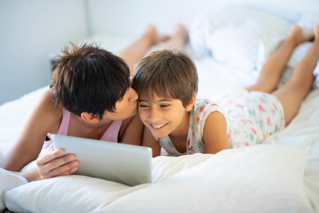 Mãe de meia-idade com sua filha de oito anos usando tablet digital no quarto.